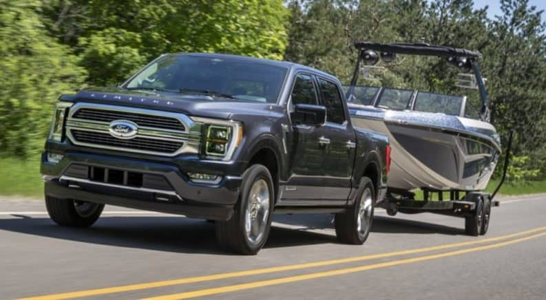A black 2021 Ford F-150 is towing a boat past trees.