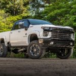 A white Chevy Silverado 2500HD Black Widow from SCA Performance is parked in front of trees.