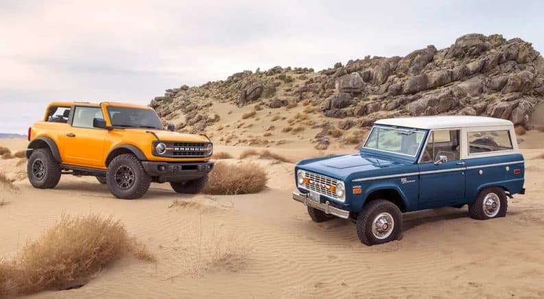 A yellow 2021 Ford Bronco 2door is parked in sand next to a blue 1970s Bronco.
