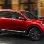 A red 2020 Honda CR-V is driving around a corner on a city street.