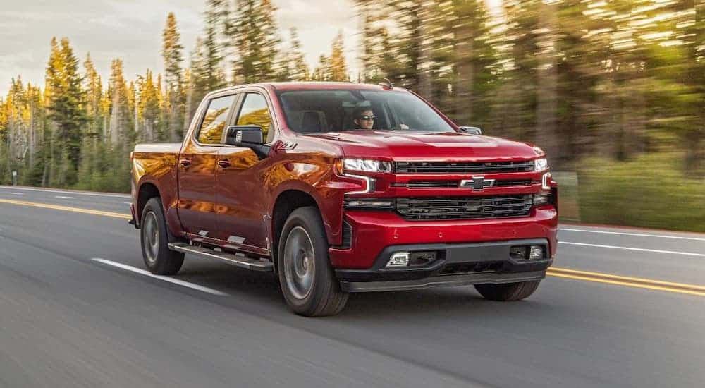 A red diesel 2020 Chevy Silverado 1500 is driving on a woodland highway.