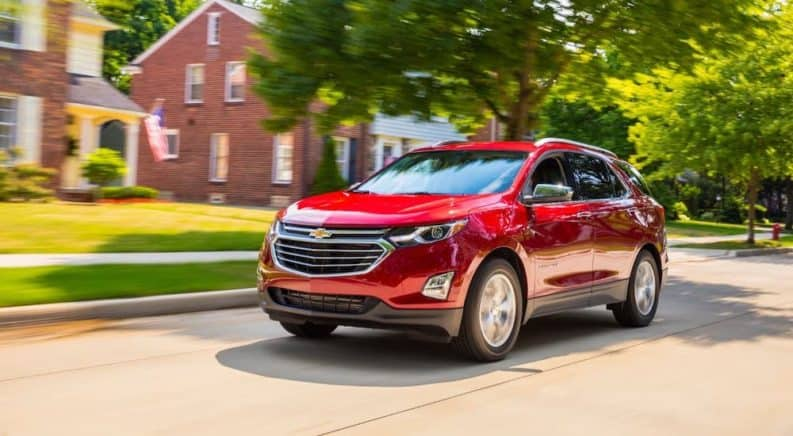 A red 2020 Chevy Equinox is driving in a suburban neighborhood.