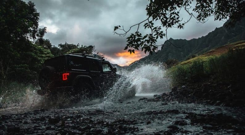 A silhouette of a 2020 Jeep Wrangler Unlimited is splashing through a river on a trail.