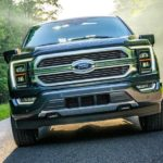 An angled photo shows the grille of a gray 2021 Ford F-150 Limited driving on a tree-lined road.