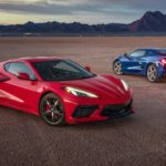 A red and a blue 2021 Chevy Corvette are parked on a flat field with mountains in the distance.
