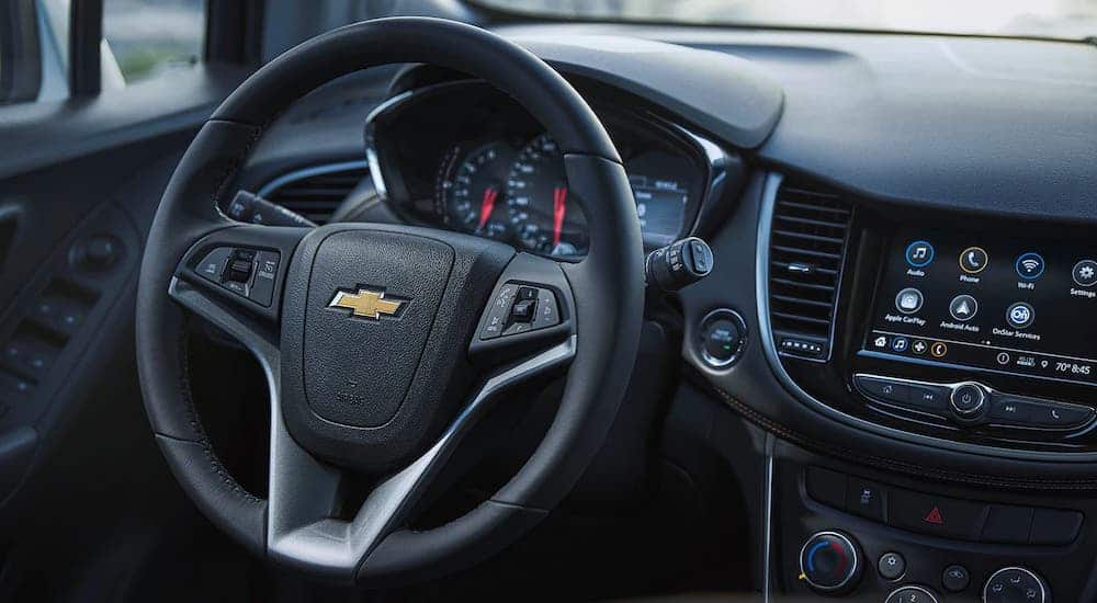 The black steering wheel and information cluster is shown in a 2021 Chevy Trax.