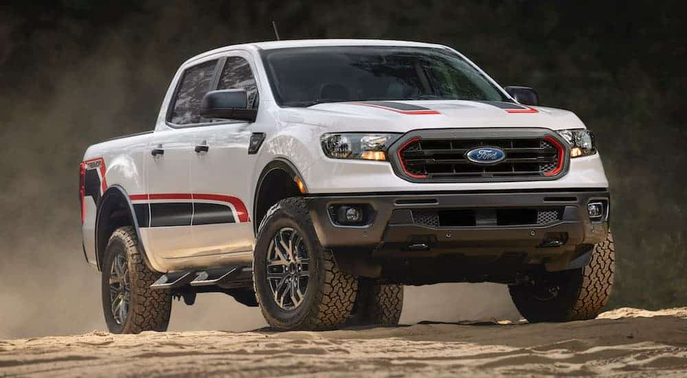 A Ford truck with a new package, a white 2021 Ford Ranger Tremor, is driving off-road on dirt.