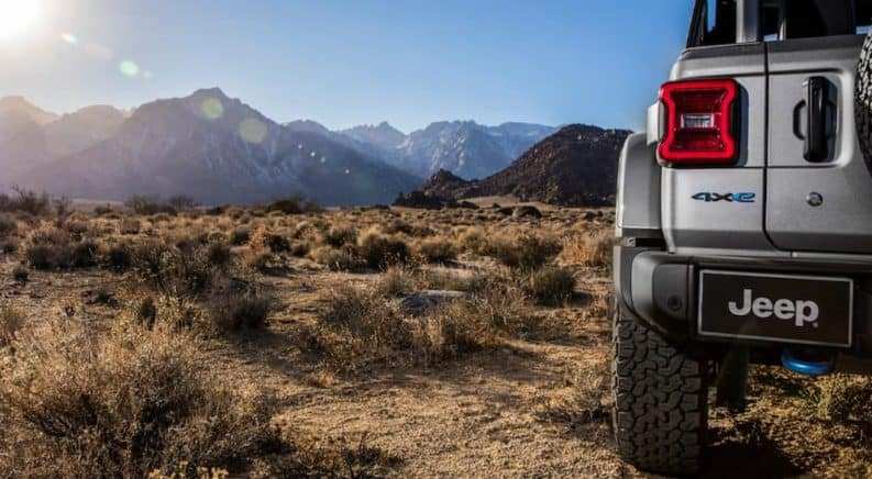 The rear taillight of a 2021 Jeep Wrangler 4xe is shown in closeup with mountains in the distance.