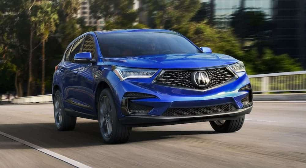 A blue 2021 Acura RDX is driving down a blurred road.