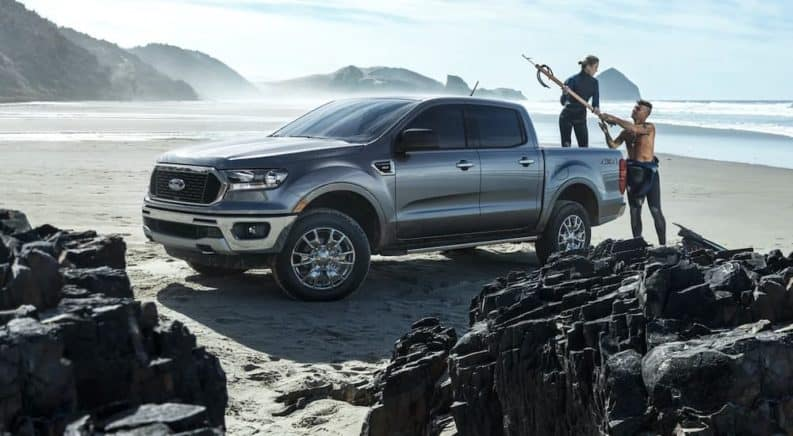 A silver 2021 Ford Ranger XLT is parked on the beach with people loading fishing gear in to the bed.