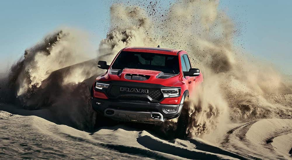 A red and black 2021 Ram 1500 TRX is driving through the dunes kicking up sand.