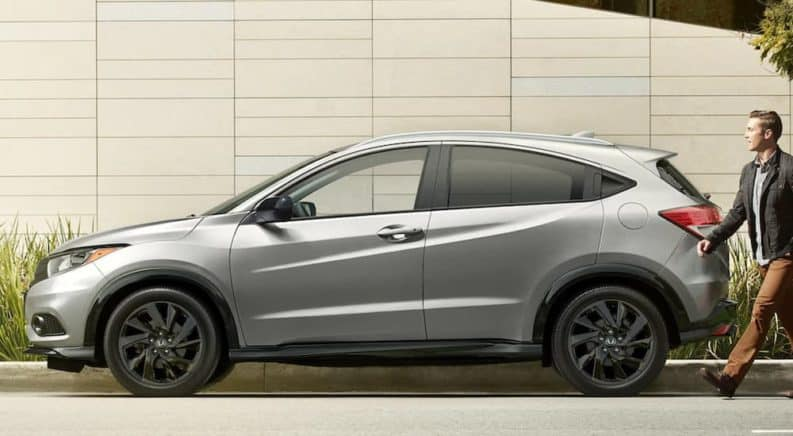 A silver 2021 Honda HR-V is shown in profile with a man approaching it from behind.