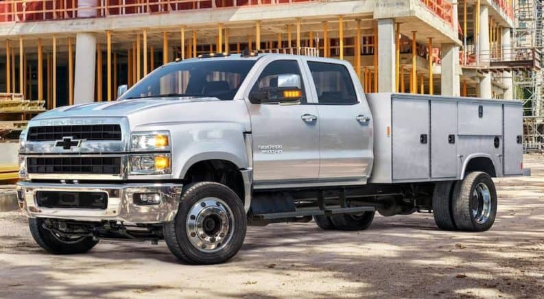 A silver 2021 Chevy Silverado 4500 is parked in front of the frame of a house.
