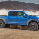 A blue 2020 Ford Raptor is driving on dirt and shown from the side.