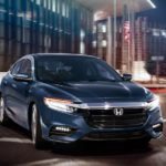 A blue 2021 Honda Insight is driving through the city at night.