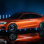 An orange 2022 Honda Civic prototype is parked in a dark warehouse in front of neon lights.