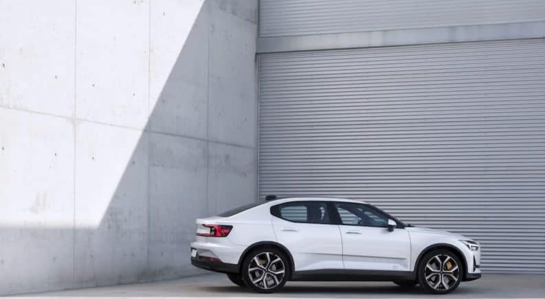 A white 2021 Polestar 2 is shown from the side parked next to a metal and concrete wall.