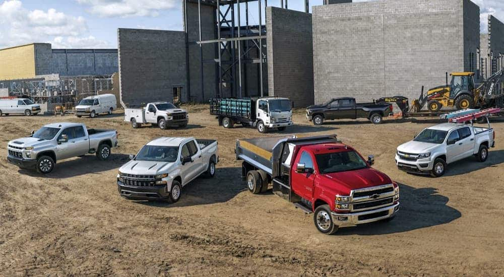 The lineup of silver, white and red Chevy commercial vehicles are shown at a job site.