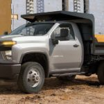 A silver 2021 Chevy Silverado 3500 HD Chassis Cab dump truck is parked in front of a job site.