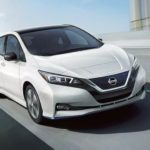 A white 2021 Nissan LEAF is driving on a highway overpass.