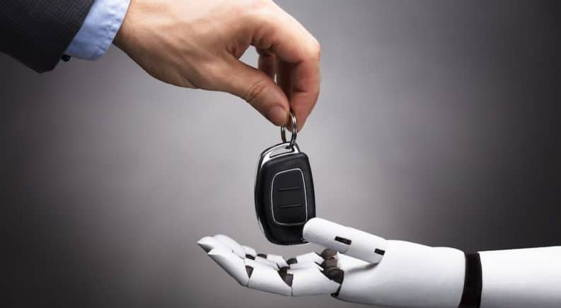 A set of car keys is being exchanged by a human and a robot.