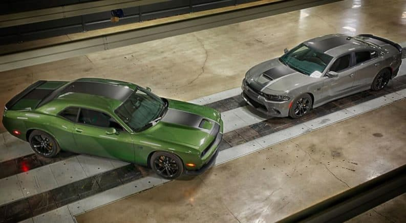 A green 2019 Dodge Challenger and a silver 2019 Dodge Charger are shown from above on a tile floor.