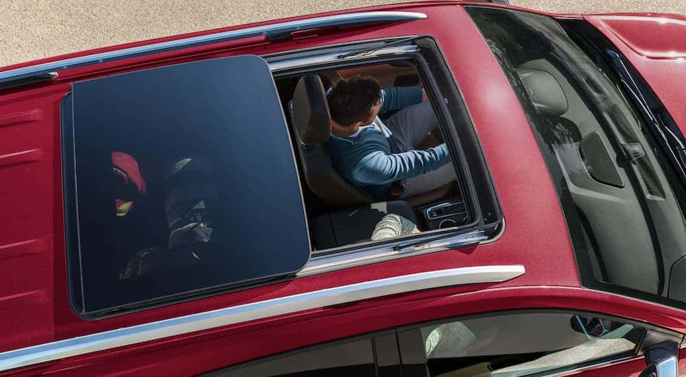 A man is shown in a red 2021 Chevy Equinox from above through the open sun roof.