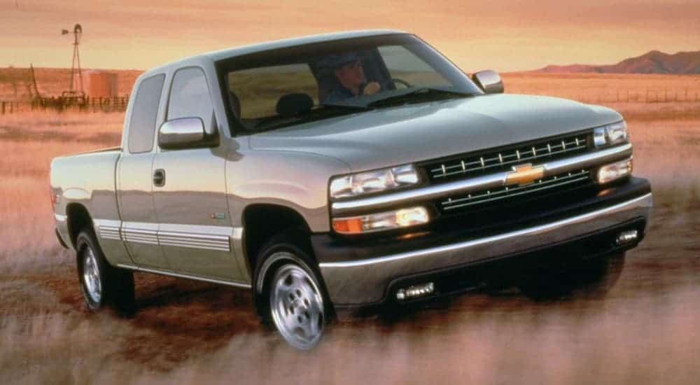 A silver 1999 Chevy Silverado 1500 is driving in a field.