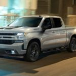 A silver 2021 Chevy Silverado 1500 is on a city street at night.