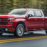A red 2021 Chevy Silverado 1500 is driving past pine trees after winning the 2021 Chevy Silverado 1500 vs 2021 Ram 1500 comparison.