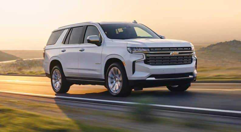A white 2021 Chevy Tahoe is driving on a rural road at sunset.