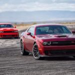 A red and an orange 2021 Dodge Challanger R/T Scat Pack Widebody are driving on a track covered in tire marks.