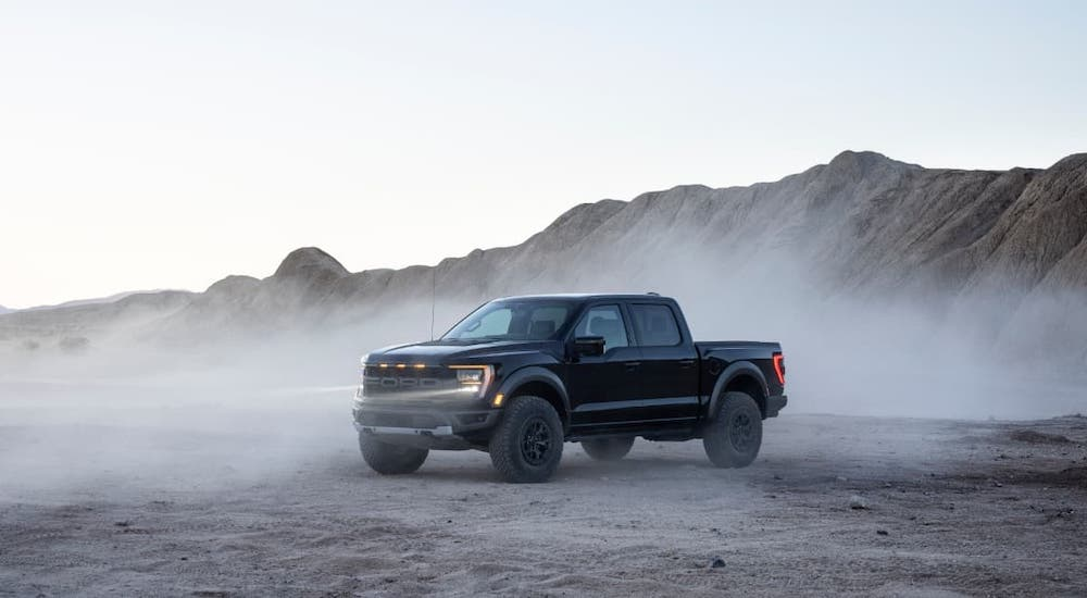 A black 2021 Ford F-150 Raptor is parked in front of a hill and a dusty desert.