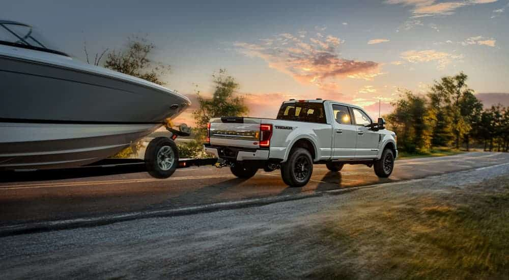 A white 2021 Ford F-250 Super Duty is towing a boat at sunset.