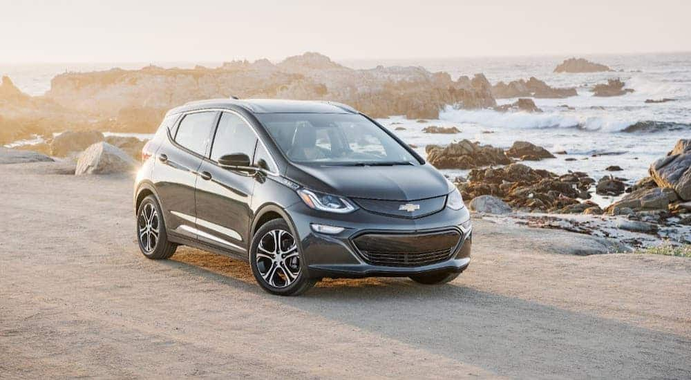 A black 2021 Chevy Bolt EV is parked on a beach.