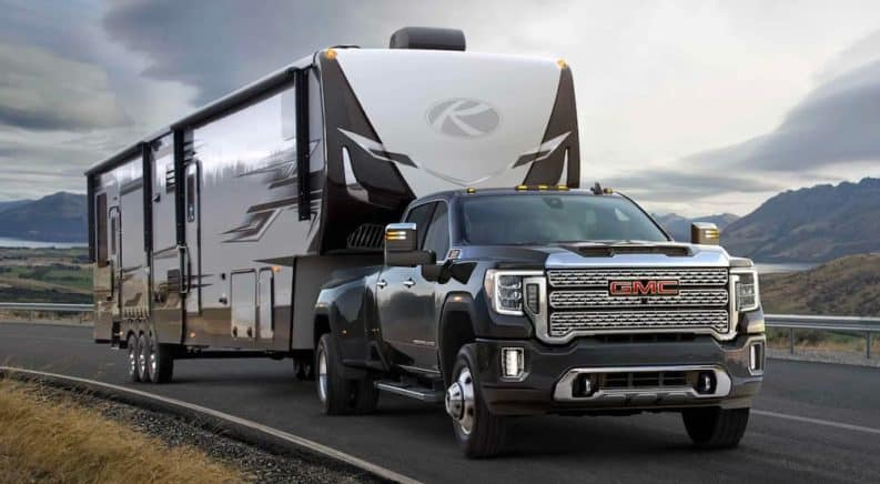 A black 2021 GMC Sierra 3500HD Denali is shown towing a large trailer after visiting a GMC truck dealer near you.