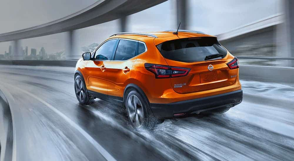 An orange 2021 Nissan Rogue Sport is shown from the rear driving on a wet bridge.