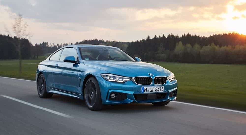 A blue 2017 BMW 4 Series coupe is driving past a field with the sun setting over trees.