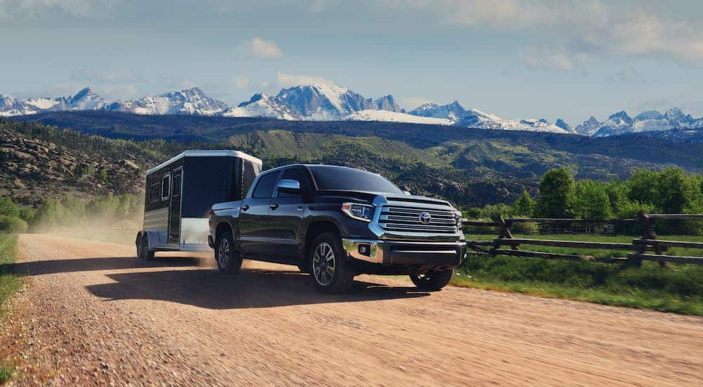 A black 2021 Toyota Tundra is towing an enclosed trailer in front of distant snow-covered mountains.