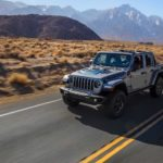A silver 2021 Jeep Wrangler 4xe Unlimited is driving on a desert highway.