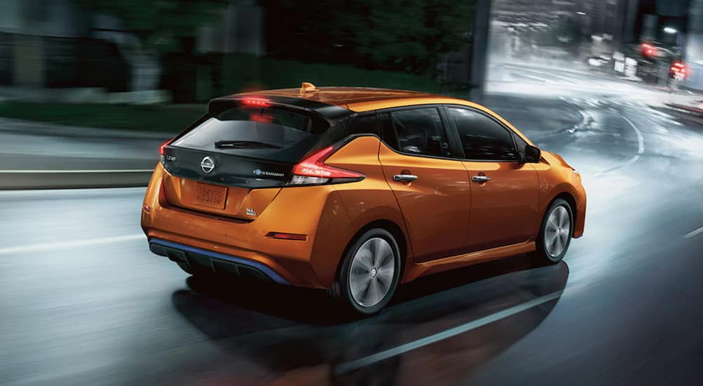 A used orange 2020 Nissan LEAF is driving through a city at night.