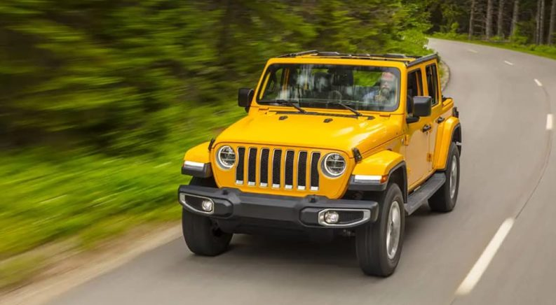 A yellow 2021 Jeep Wrangler is driving down a winding road after leaving a used Jeep dealer