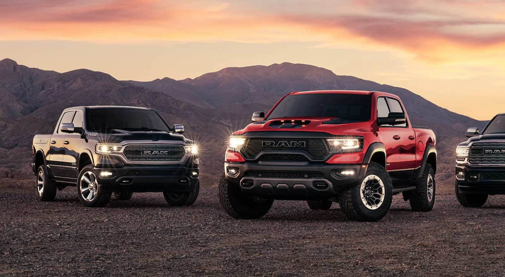 A row of Ram 1500 trucks are parked in front of mountains.