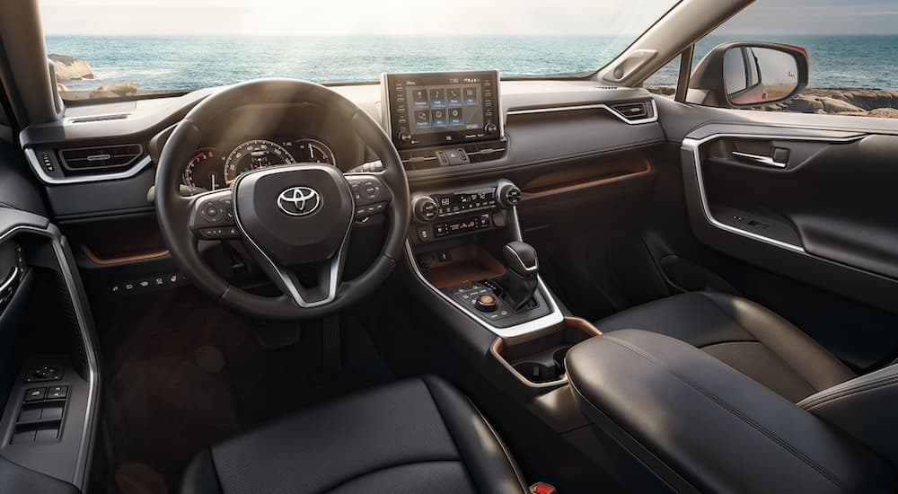 The interior of a 2021 Toyota RAV4 shows the steering wheel and infotainment screen.