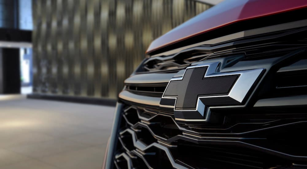 A close up of the front grille of a red 2022 Chevy Equinox shows the Chevy bowtie.