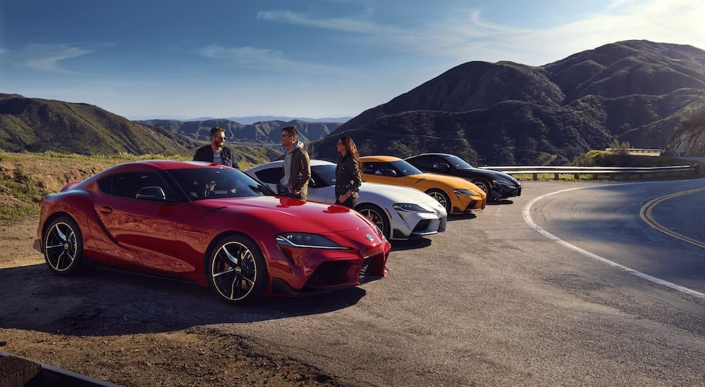 A reed, a white, a yellow, and a blue 2021 Toyota GR Supra are parked in a row around a corner.