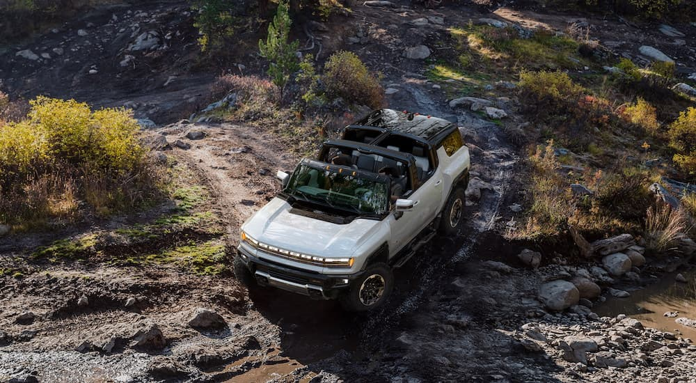 A white 2023 GMC Hummer EV SUV is shown from a high angle driving on a muddy path.
