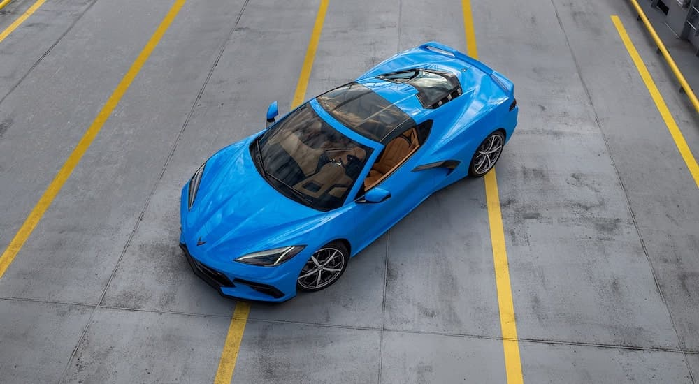 A blue 2022 Chevy Corvette is shown from a high angle in a lot after leaving a Chevrolet dealer.