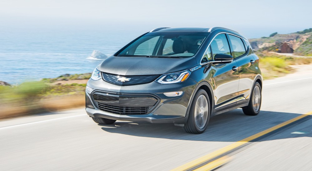 A grey 2019 Chevy Bolt EV is driving on a road next to the ocean.