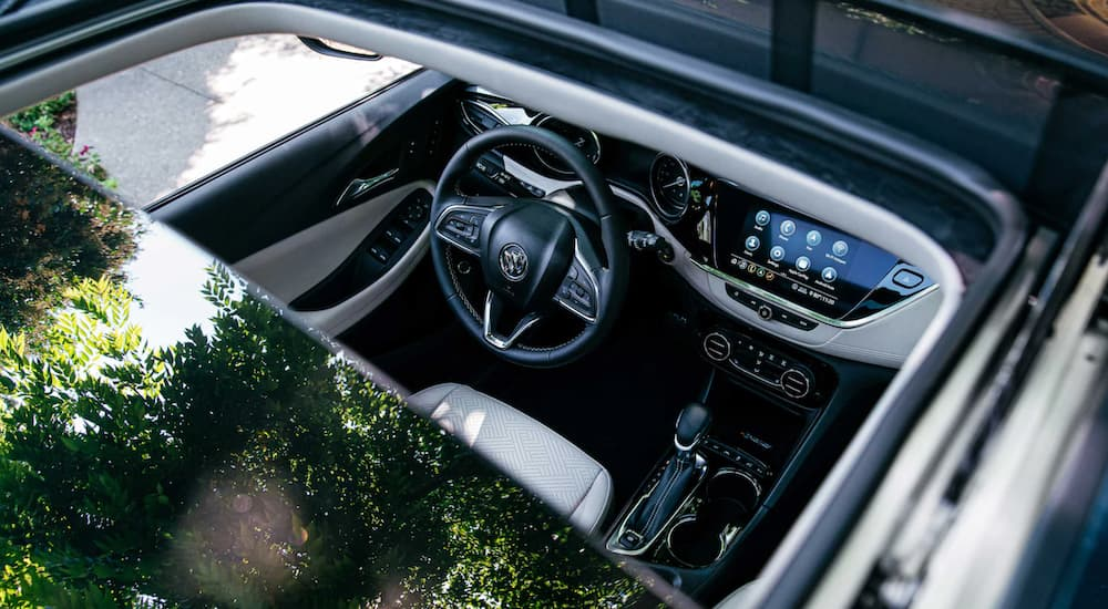 The white and black interior of a 2022 Buick Encore GX is shown through the moonroof.